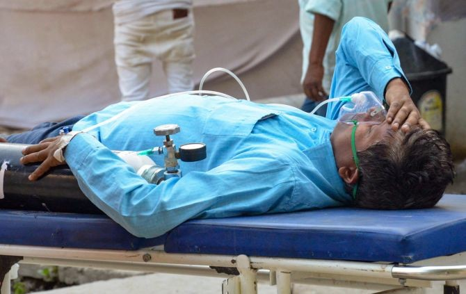 Relatives carry a COVID-19 patient on oxygen support for admission at the SKMCH Medical College and Hospital, Muzaffarpur, Bihar. Photograph: PTI Photo